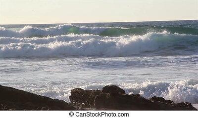 Quick waves rushing to the shore splashing on big rocks -...