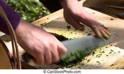 Quickly chopping basil with a large knife - A cook quickly...
