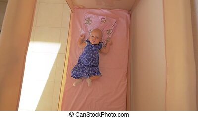 Quiet baby girl in playpen