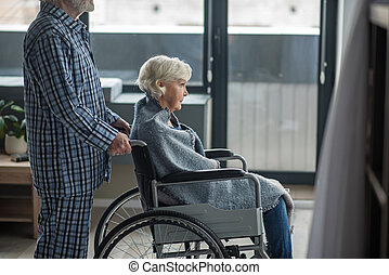 Quiet disabled woman with man looking outside