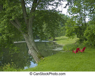 A tranquil scene of two old lawn chairs near a pond on a nice Summer day.