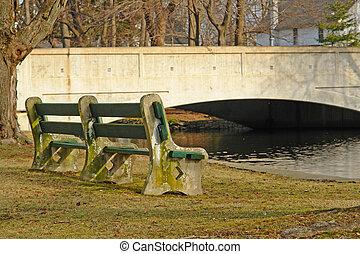 Park bench next to a stream with a bridge.