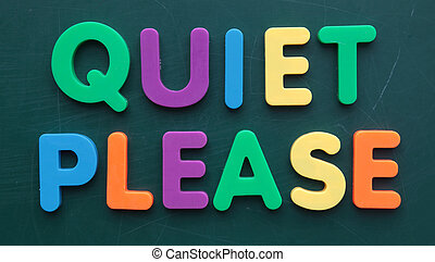 The term quiet please in colorful letters on a blackboard.