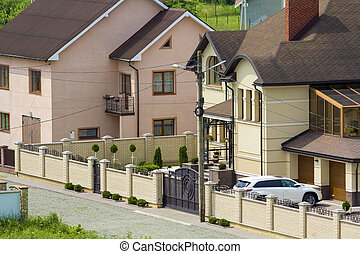Quiet residential area with new expensive two- story cottages with brick fence and tile roofs and white sport car parked in front of garage door in paved well-kept yard. Luxury and prosperity concept.