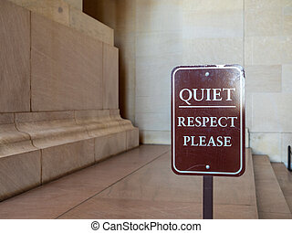 Quiet, respect please brown sign in front of a decorative display