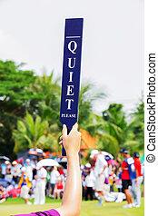Quiet sign in golf tournament - Volunteer holds up a Quiet...