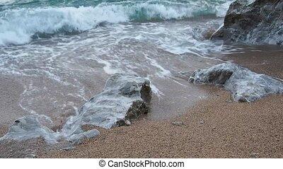 Quiet surf - quiet sea surf breaking on big boulder