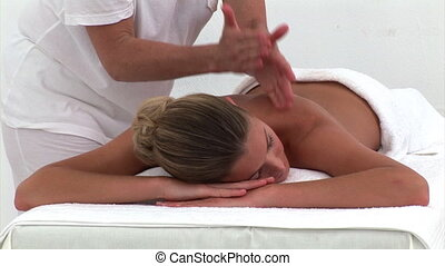 Quiet woman enjoying a back massage in a spa center