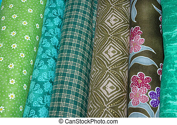 Bolts of quilting fabric in the green range.