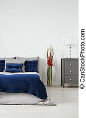 Quilted cushions in dark blue and organic cotton linen in gray on a bed in a minimal style bedroom interior. Empty white wall background. Real photo.