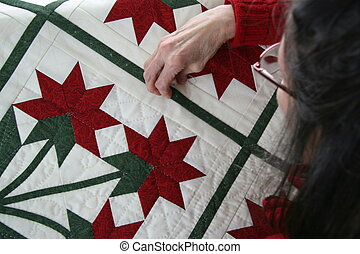 Woman hand quilting red and green tone quilt