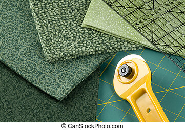 Quilting supplies: green materials, rotary cutter, pad and ruler.