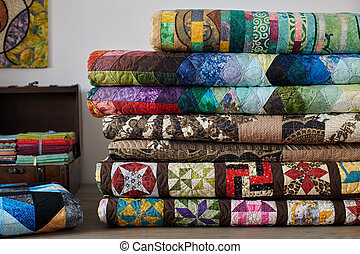 Quilts stacked and wooden chest with stacks of fat quarters on white wall background