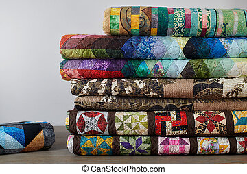 Quilts stacked on white wall background