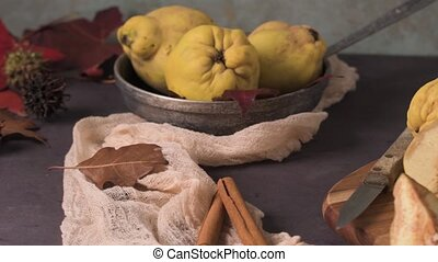 Quince fruits and marmalade in a ceramic bowl on table top.