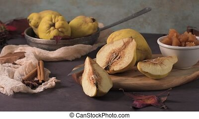 Quince fruits and marmelade in a ceramic bowl on table top.