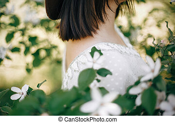 Quince white flowers on tree branch and shoulder of boho ...