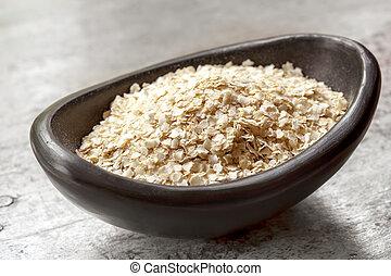 Quinoa Flakes - Quinoa flakes in small black bowl over...
