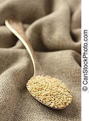 Quinoa grain in metal spoon on sackcloth background