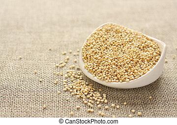 Quinoa grain in white ceramic bowl on sackcloth background
