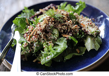 Quinoa salad with vegetable on wooden table