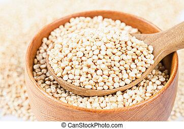 quinoa seeds in wooden spoon.
