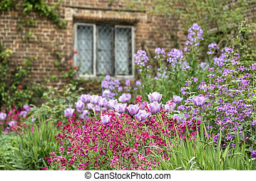 Quintessential vibrant English country garden scene landscape with fresh Spring flowers in cottage garden