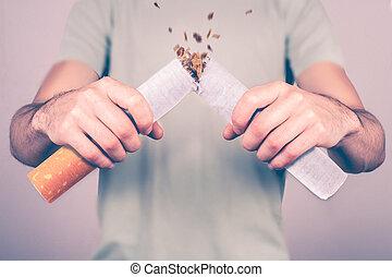 Quit smoking - male smoker breaking giant cigarette