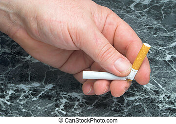 Quit Smoking - A person breaking a cigarette, signifying...