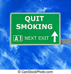 QUIT SMOKING road sign against clear blue sky