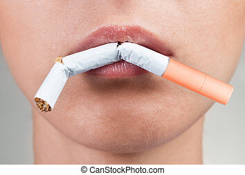 Quitting smoking - Female lips holding a broken cigarette,...