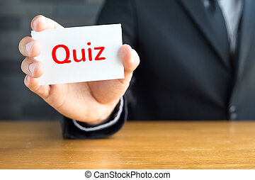 Quiz, message on white card and hold by