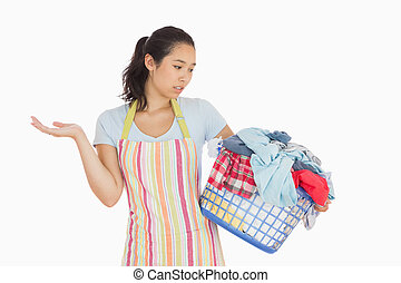 Quizzical looking young woman looking at basket - Quizzical...