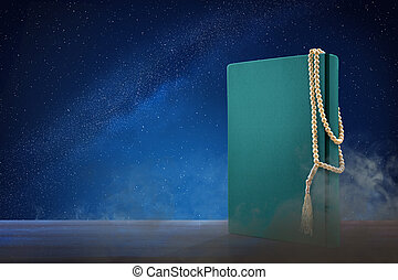 Quran and prayer beads on wooden table at outdoor