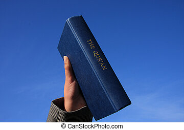 Qur\\\'An On Blue Sky - A copy of the Koran held up against...