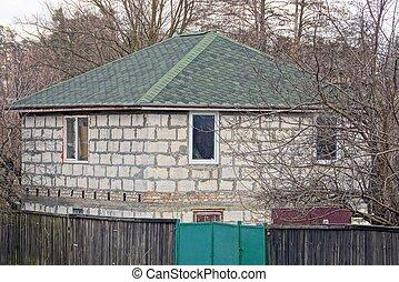 része, egy, szürke, tégla épület, noha, egy, zöld, cserép tető, noha, növényzet, és, bitófák, mögött, egy, kerítés
