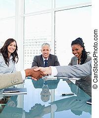 réunion, femmes affaires, mains, regarder, sourire, collègues, secousse