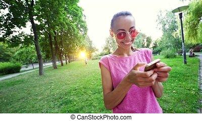 różowy, monokle, młody, telefon, zielony, ruchomy, uśmiechanie się, używając, reputacja, park, zachód słońca, kobieta, miasto, tło