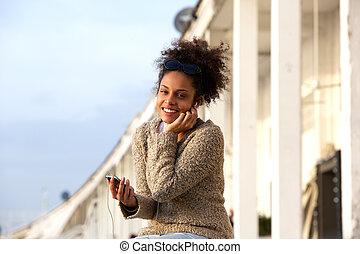 rörlig telefonera, kvinna, lyssnande, hörlurar