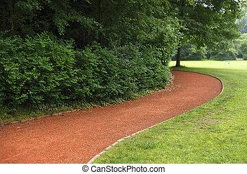 Weg mit rötlichen Bodenbelag im Park
