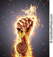 ręka człowieka, w, niejaki, ogień, jest, przytrzymując, złoty, medal., zwycięzca, w, niejaki, competition.