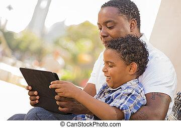 raça misturada, pai filho, usando, almofada toque, computador, tabuleta