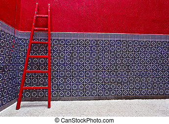 Rabat, Morocco: Colorful riad interior with red ladder and blue ceramic tiled wall in Rabat, Morocco.