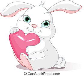 Small lovely rabbit holds love heart