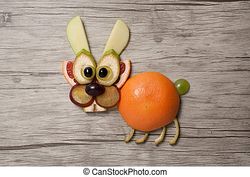 Rabbit made with fruits on wooden background