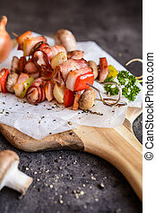 Rabbit meat, bacon and vegetable skewers