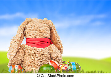 Rabbit, sit on green grass and group of colorful eggs are behind