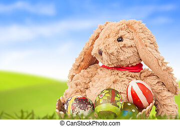 Rabbit, sit on green grass and group of colorful eggs are behind with blue sky background for happy easter festival