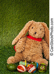 Rabbit, sit on green grass with group of colorful eggs, can use
