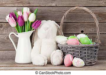 Rabbit toy, easter eggs and colorful tulips